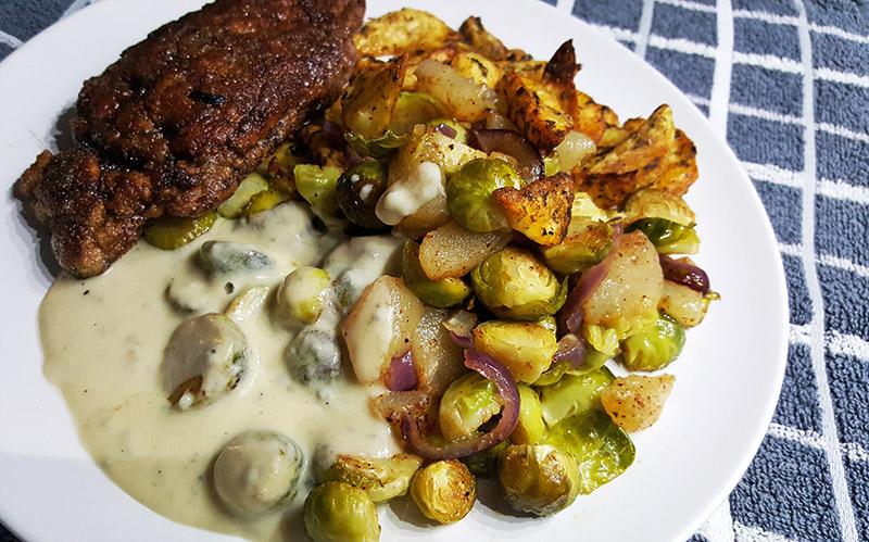 Zelfgemaakte kipschnitzel met gorgonzolasaus en aardappelen en spruitjes uit de oven