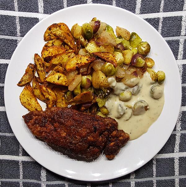 Zelfgemaakte kipschnitzel met gorgongolasaus en aaradeppel, spruitjes en peer uit de oven