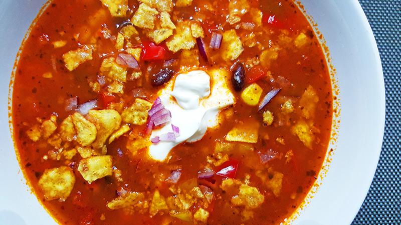 Mexicaanse zwarte bonensoep met mais, tortillachips en zure room